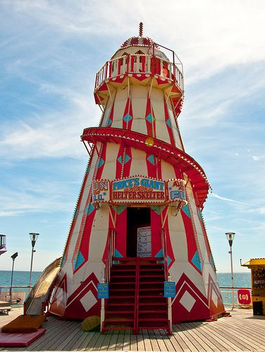A traditional helter-skelter funfair ride which is painted in bright bold colours.