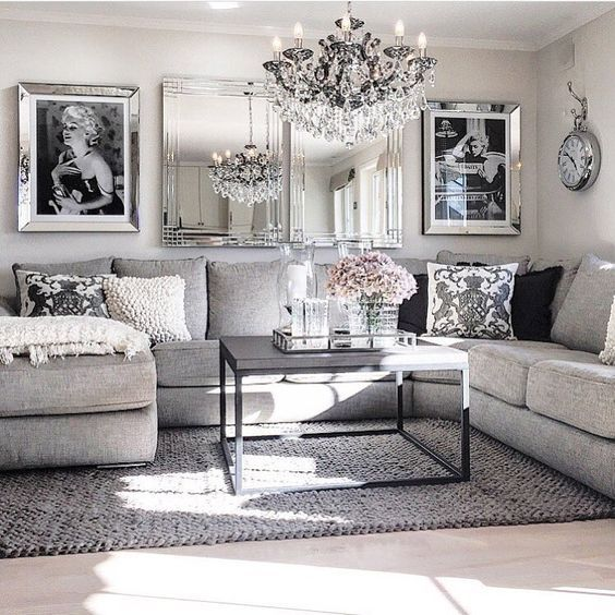 Living Room decor ideas - glamorous, chic in grey and pink color palette with sectional sofa, graphic black & white photography and crystal chandelier.