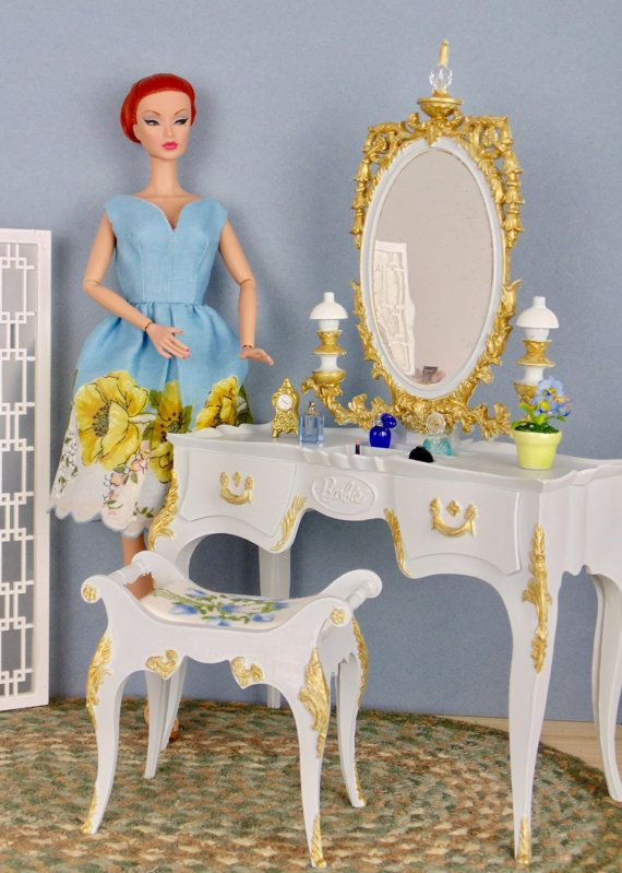 This vintage Suzy Goose Barbie vanity and matching bench seat have been completely repainted in crystal blue and gold acrylic paint. After painting, pieces were sealed with poly acrylic matte finish sealer. Cushion on bench was made from a vintage embroidered hankie. Original mirror finish has minor blemishes, much like a real vintage mirror would. Drawers on the front of the vanity open.  Doll, screen divider, flooring, rug, and objects on vanity are for display purposes only and are not…