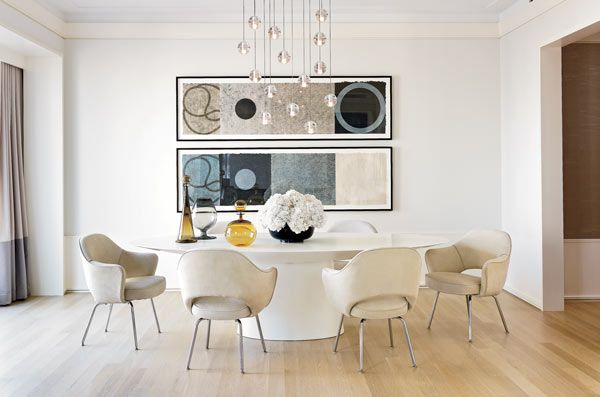 Designer Jessica Lagrange created a softly minimalist tableau with a lacquered pedestal table and Knoll Saarinen chairs on a bare floor and a 14-pendant Bocci chandelier.