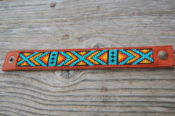 Native American loom beaded genuine leather bracelet.  Made in loom bead technique with turquoise blue, orange, yellow and black size 11/0 Czech seed beads. Sewed on genuine brown chamois leather.  Metal snap closure.  Width - 3 cm (1,2 inches). Please write me a message, or leave a note during checkout - what size you need.  How to measure your wrist? Wrap a tape measure or a piece of string around your wrist so it is snug but not overly tight. Don't add anything extra to the measurement —…