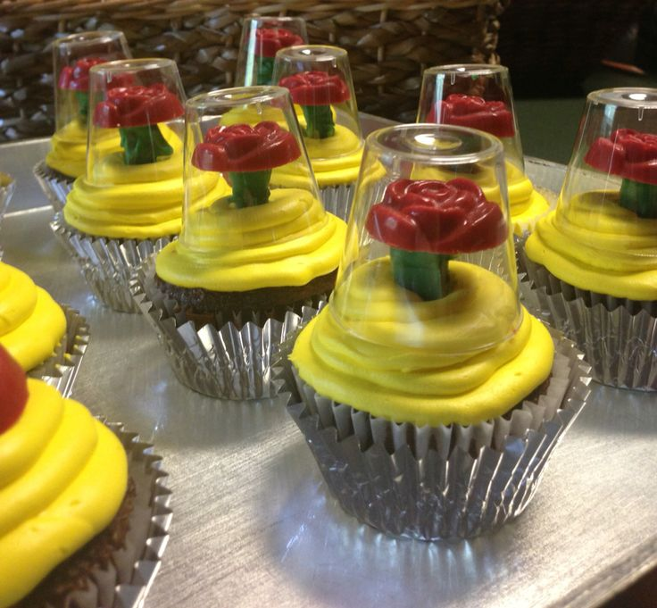 Beauty and the Beast cupcakes. Create the flower using a piece of a green candy coated pretzel rod and top it with a red candy mold flower. Top the flower with a small plastic shot glass.