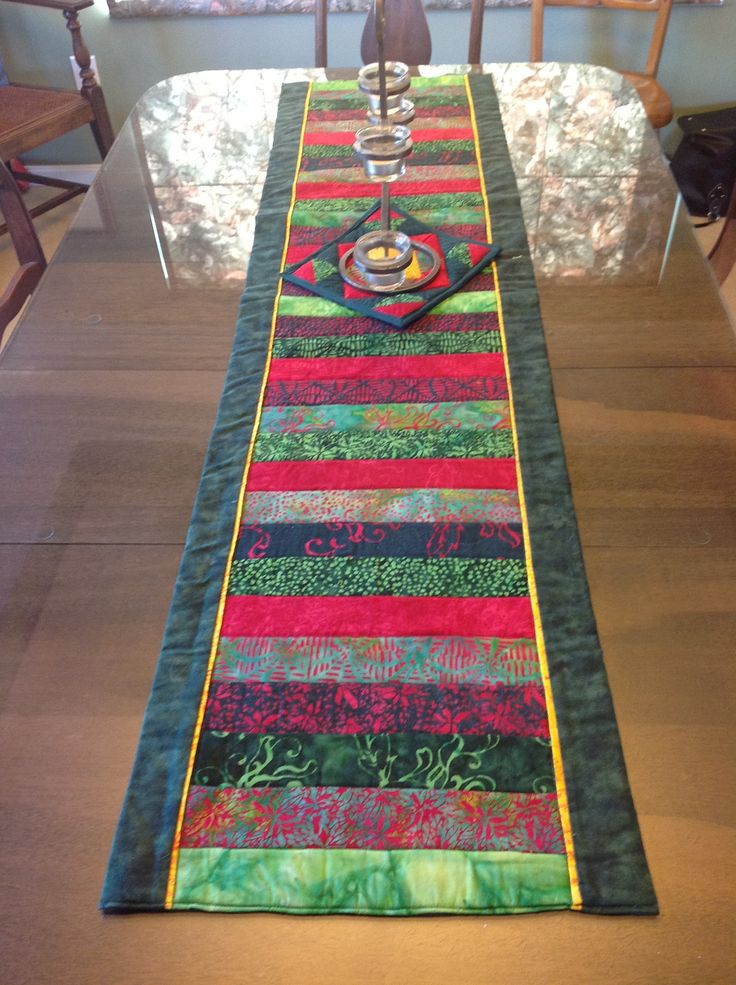 """Pinner wrote, """"This is the christmas table runner I made with a jelly roll of batiks.  I adapted a pattern I found on all people quilt for a blue table runner.http://www.allpeoplequilt.com/projects-ideas/table-toppers-runners/batik-strips-table-runner-quilt_1.html"""""""
