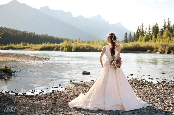 Rocky Mountain bride on the Bow River in Canmore | Calgary wedding photographer Tara Whittaker | Bouquet from @flowersbyjanie | @romonakeveza gown from @cameo