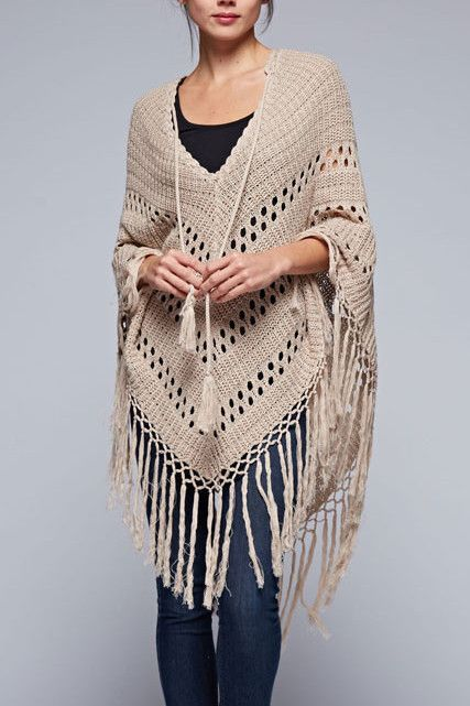 This bohemian inspired crochet poncho has a long tassel tie in front and long fringed hemline. Ultra soft cotton/acrylic blend yarn in a soft, neutral tone to