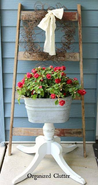 Old bed spring wreath and a wonderful planter made from a galvanized tub with a pedestal table bottom! :)                                                                                                                                                     More