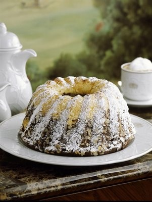 """Gugelhupf is a big cake, derived from the Groninger Poffert, and has a distinctive ring shape or the shape of a torus. It is usually eaten with coffee, at coffee breaks. Gugelhupf consists of a soft yeast dough which contains raisins, almonds and Kirschwasser cherry brandy. Some also contain candied fruits and nuts. In Upper Austria it has a different name: """"Wacker"""" or """"Wacka""""."""