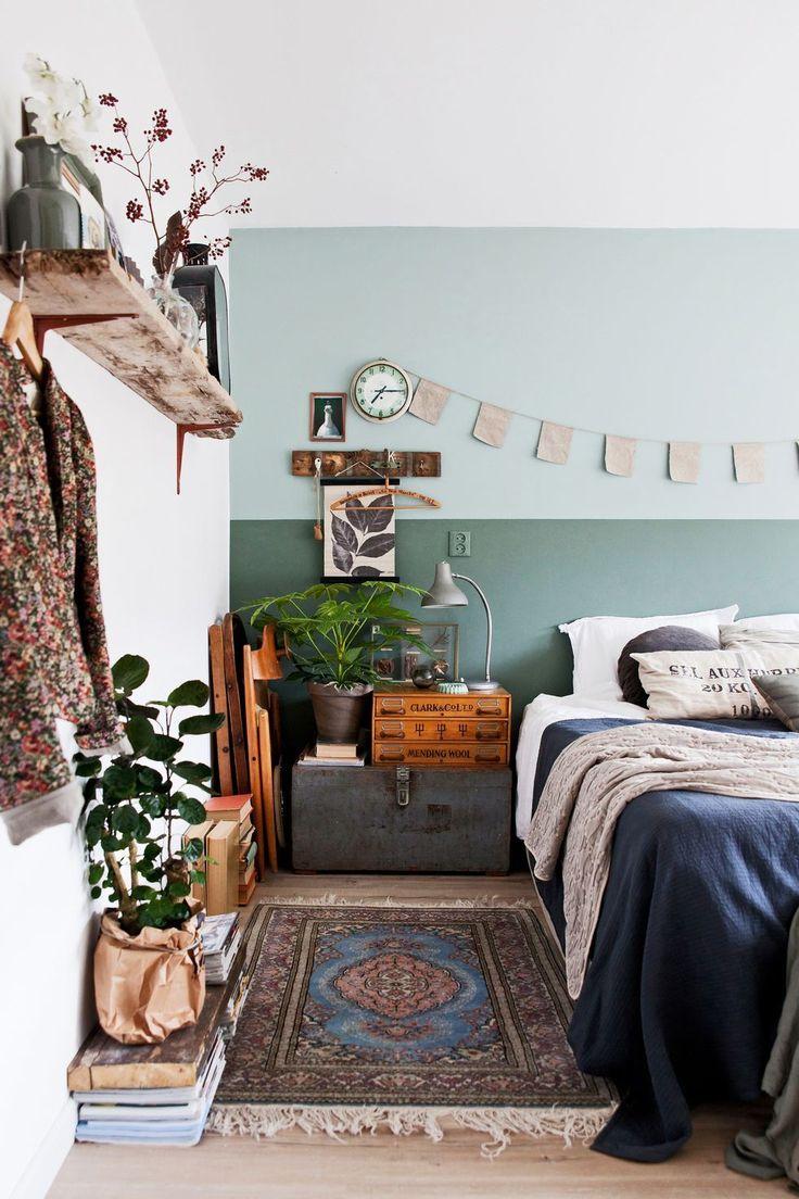 Schlafzimmer im Boho Vintage Look mit geüner Wand, Kelim Teppich und Akzenten aus rustikalem Holz