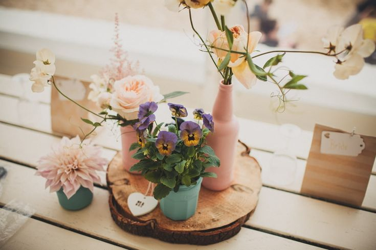spray painted pink & mint green bottles on wood planks with wild flower stems - Image by Ali Paul Photography - Bohemian wedding dress from Grace loves Lace at a laid back coastal beach wedding in Cornwall. Bridesmaids wear duck egg blue dresses from H&M and groomsmen wear jeans, flip flops and braces.