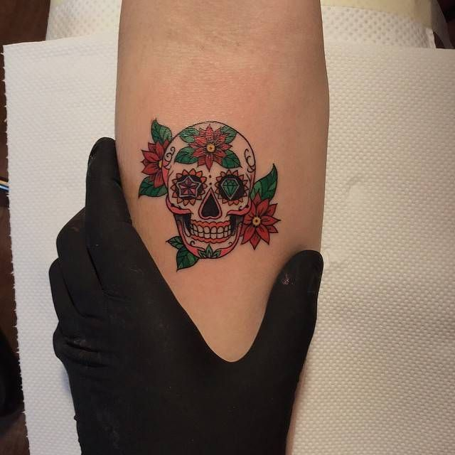 Illustrative sugar skull tattoo on the right inner forearm.