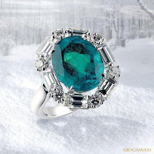 Mouawad. A halo of white diamonds embracing a vivid green natural emerald.