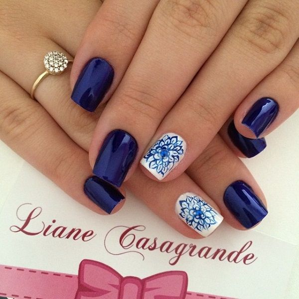 Dark blue metallic nail art design with floral details on top. White nail polish is used as base to contrast the dark blue flower details.