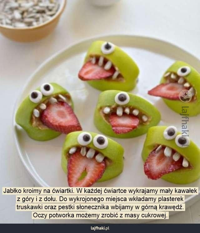 Straszne danie na Halloween - Jabłko kroimy na ćwiartki. W każdej ćwiartce wykrajamy mały kawałek z góry i z dołu. Do wykrojonego miejsca wkładamy plasterek truskawki oraz pestki słonecznika wbijamy w górną krawędź. Oczy potworka możemy zrobić z masy cukrowej.