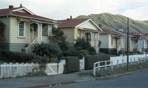 # HISTORY # State houses | NZ - 1980s. Different architectural detailing around porches, and the use of hipped and gabled roofs, distinguish each house.