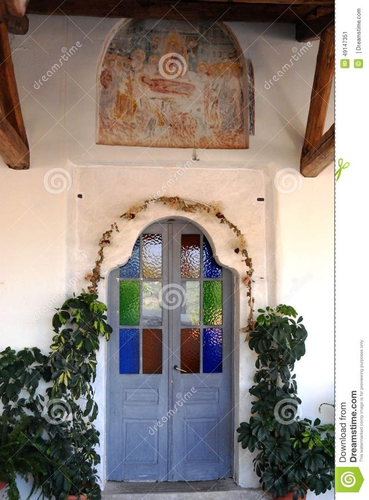 The peninsula of Pylos in Greece is characterized: the long and beautiful white sand beaches; small and beautiful coves and quiet but majestic presence of significant mountain flora. Pelion has something to offer to all the questions of the visitors.  Photo taken in a small mountain village, which is located inside of the peninsula called Milies. The photo depicts the entrance door from the stained glass windows, the small Orthodox church in the country.