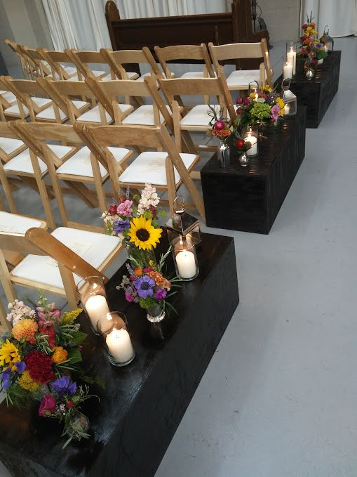 Dark wood columns laid horizontally to hold aisle decor
