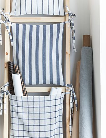 Upcycled ladder turned into a storage unit with pockets made from IKEA tea towels.