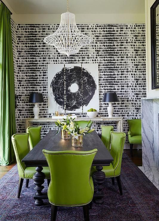 Black and green dining room features a white lantern hanging over a matte black dining table lined with green leather dining chairs with brass nailhead trim atop a purple Persian rug placed in front of a marble fireplace under a black beveled mirror.