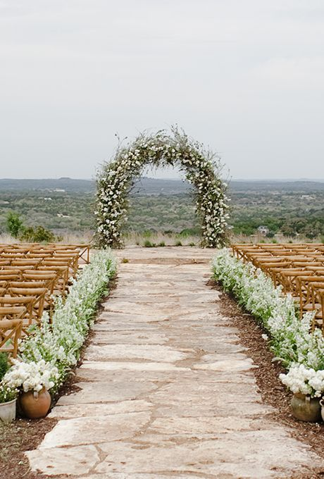 A handmade ceremony arch of blooming cherry and pear branches | Brides.com