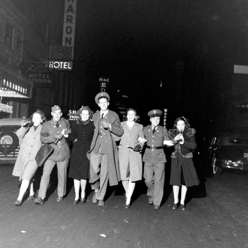 A group celebrates New Year's Eve on the streets of New York. 1941/42