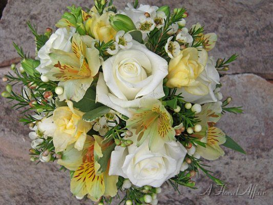 BB0266-White Rose, Yellow Freesia, and Alstroemeria Bridal Bouquet    Ivory roses, yellow freesia, yellow alstroemeria, and waxflower.