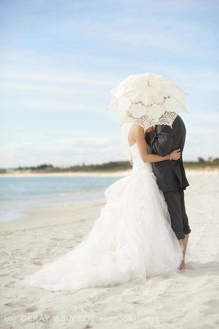 Romantic and relaxed. Kissing behind a parasol. Bride & Groom photos on the beach
