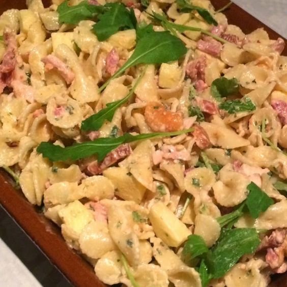 Koude pastasalade  250 gram pasta - 100 gram uitgebakken spekjes - halve (75 gram) gerookte kipfilet in stukjes - 1 appel in stukjes - stukjes gedroogde tomaat - half bakje gemengde noten  - rucola sla - saus