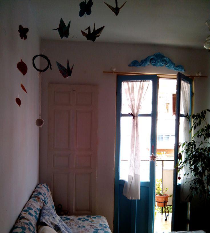 Móvil de grullas, restos de puertas, plantas