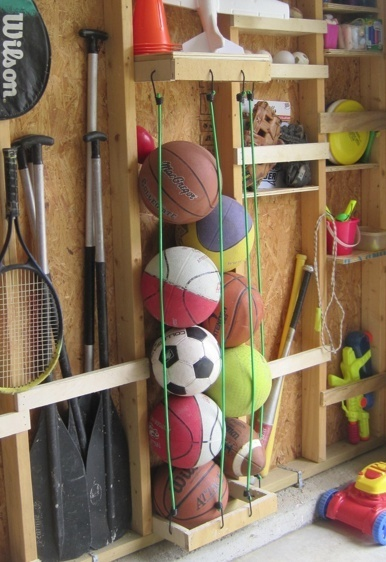 Some pieces of wood and stretchy cords and viola! A great way to organise balls in your garage. #storage #organizing #clutter #garage. [ #GarageDoorTrends, #GarageDoorStyles, #GarageDoor, #OverheadDoor, #Canada, #Saskatchewan, #Regina, #Saskatoon, #ODCS, #ODCSaskatchewan ]