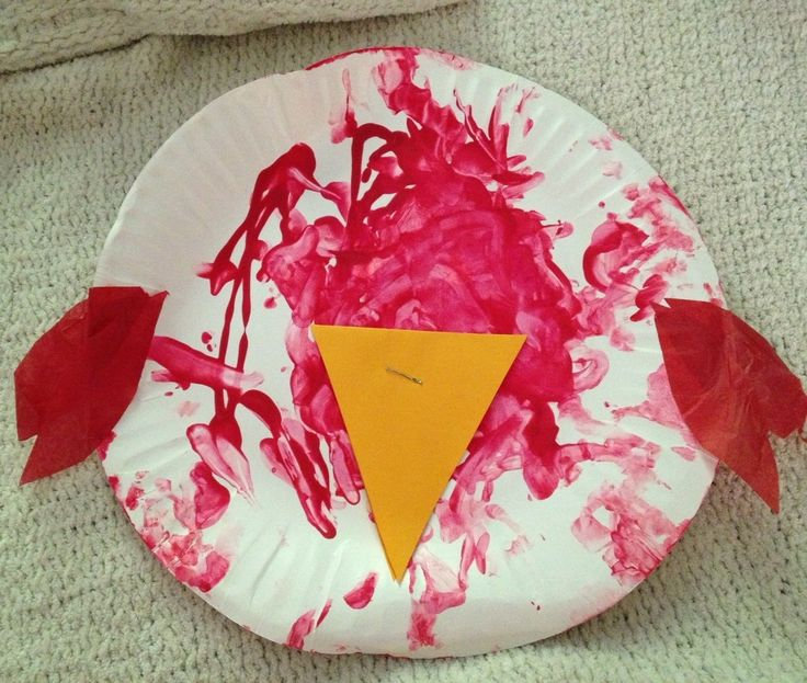 A KinderCare toddler creates a bird with the help of his teacher. The student paints the plate and then the teacher helps assemble the keepsake to take home.