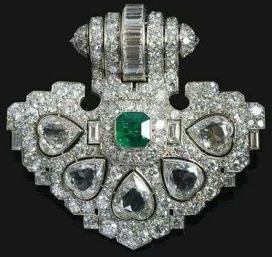 Un important clip en platine et diamants, serti de cinq diamants en cœur de taille ancienne avec en son centre une émeraude taillée à degrés, pouvant se porter en pendentif par l'ajout dune bélière. Par René DUFOUR,  Ca. 1930
