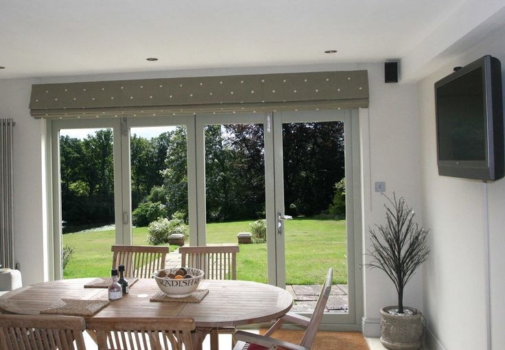 Kitchen with bifold doors with Classic Roman Blind in Moghul embroidered cotton Jinda Spot in Stone.
