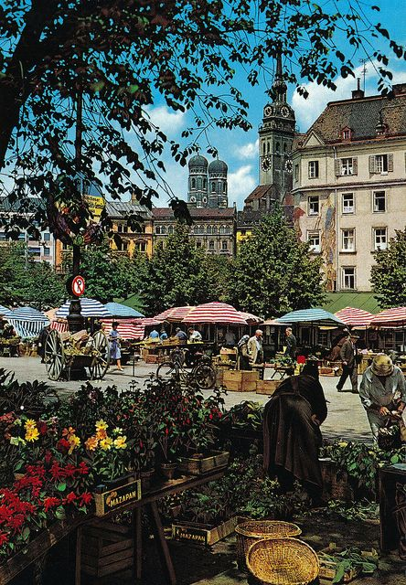 Viktualienmarkt in Munich with the Frauenkirche in the background. Come here every day of the week to buy top quality groceries and enjoy the real Bavarian flair.