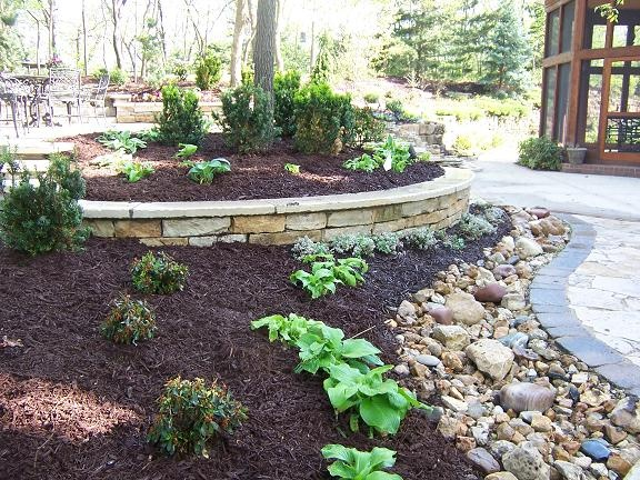 Like the stone wall and the rock bed. Could be good for drainage.