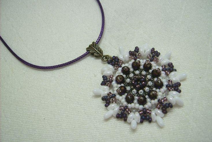 Ny-560. Lila és fehér üveg gyöngyös, bronz fém alapra hímzett medál, lila színű nyaklánc alapon. A nyaklánc hossza: 45 + 5 cm. A medál mérete: 54 x 45 mm. Ára: 850.-Ft.