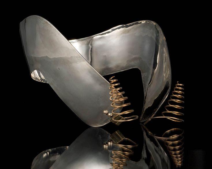 Zilveren oorijzer met gouden krullen en gouden stiften uit Staphorst, gedragen door vrouw of meisje van gegoede komaf. Gouden stiften en klinknagels waren slechts voorbehouden aan enkele welgestelde families. Oorijzer is vervaardigd in 1954 door F.G.A. Drost te Staphorst. Hij gebruikte tijdens eerste decennia van werkzame periode meesterteken van moeder, A.J. Drost-Keus. Haar meesterteken was aangepaste meesterteken van haar in WWII omgekomen man A.O. Drost. #Overijssel #Staphorst