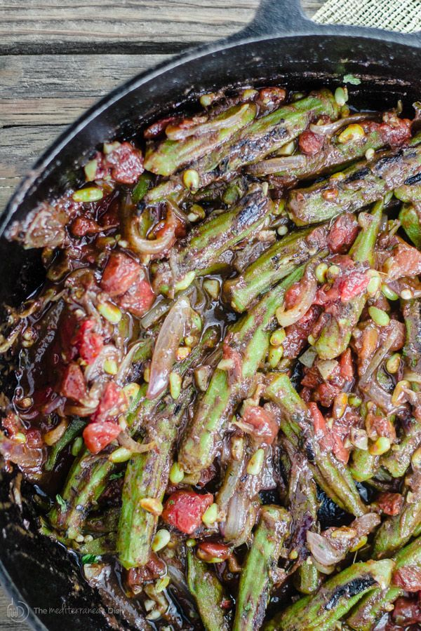 Mediterranean One Skillet Okra and Tomato Recipe | The Mediterranean Dish. Okra and tomatoes with garlic, onions, sumac and crushed red peppers. Garnish with toasted pine nuts and crushed mint. Out of this world! Easy. Vegan. Gluten Free. Get the step-by-step today.