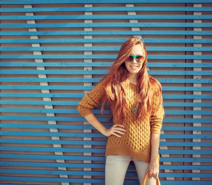 Beautiful young red-haired young girl in sunglasses standing near the wall of blue wooden planks summer warm day