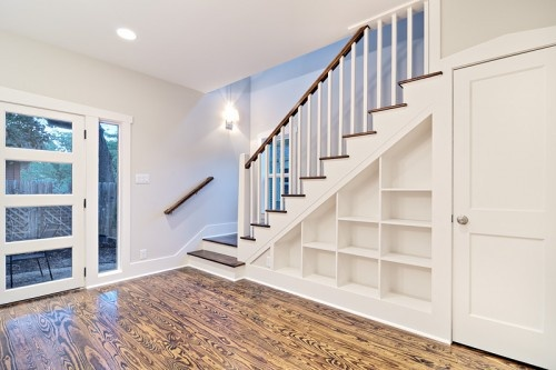 """Shelves under the stairs; add doors to """"close"""" the space.  or use drawers, which will make for a cleaner look"""