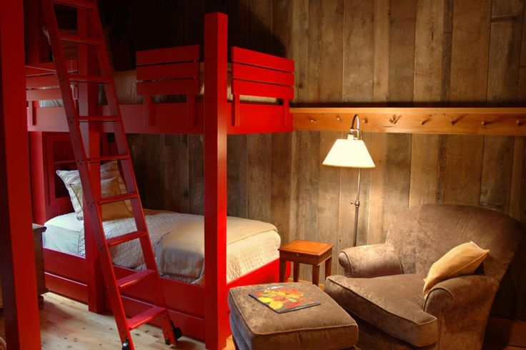 Red bunk beds add a pop of color to the kids' room in HGTV Dream Home 2006. Weathered wood paneling and pine floors add to the rustic, bunkhouse feel. A suede armchair and ottoman provide a cozy seating nook.