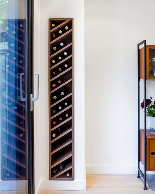 Carefully detailed custom walnut wine rack is slotted discretely into the living room wall