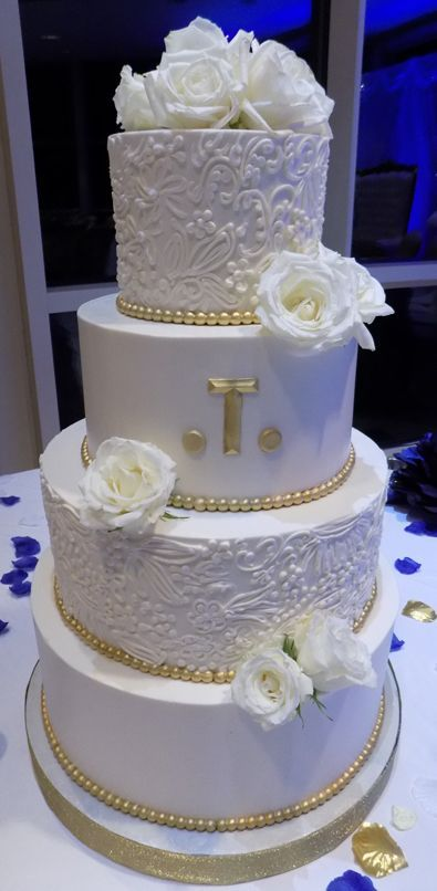 4 Tier buttercream wedding cake decorated with buttercream lace, edible gold borders and fresh roses. #goldweddingcakes