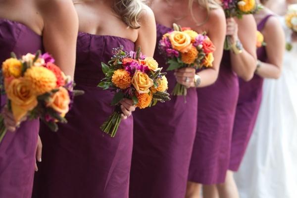 Bridesmaids in spiced wine jcrew dresses with orange purple bouquets