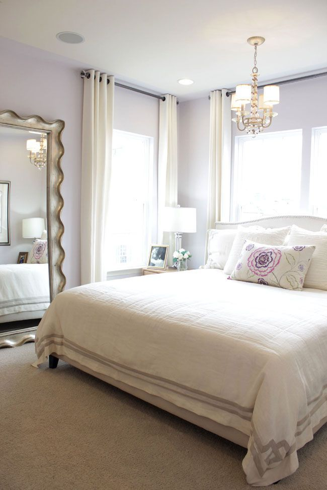 By using a large wall mirror, hanging the drapery rods higher above the window with light window treatments, this space seems a lot larger. I love this #bedroomdecor