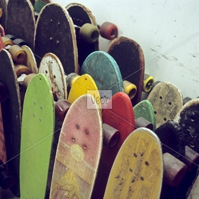Rows of used skateboards leaning against a wall by fStop Photography