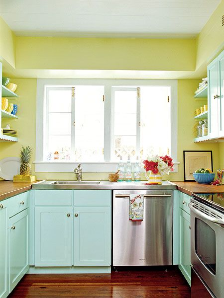 A tropical aqua paint gave inexpensive wood cabinetry an appealing, authentic look in this Key West, Florida, kitchen. The counters are pine from a 1920s Palm Beach Hotel. (Photo: Tria Giovan)  Wall paint: Hibiscus (2027-50) by Benjamin Moore; Cabinet paint: Aquatint (6936) by Sherwin-Williams