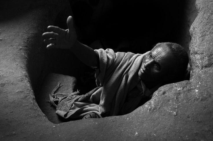"""""""En la luz"""". Un peregrino emerge de un túnel subterráneo que conecta iglesias rupestres monolíticas de Lalibela, Etiopía. Se cree que el cambio de una total oscuridad en luz para curar e iluminar a los que pasan por el túnel. Durante la Navidad ortodoxa en enero de miles de peregrinos etíopes viajar a Lalibela, muchos a pie, para participar en las celebraciones de la antigüedad. Ubicación de la fotografía: Lalibela, Etiopía."""