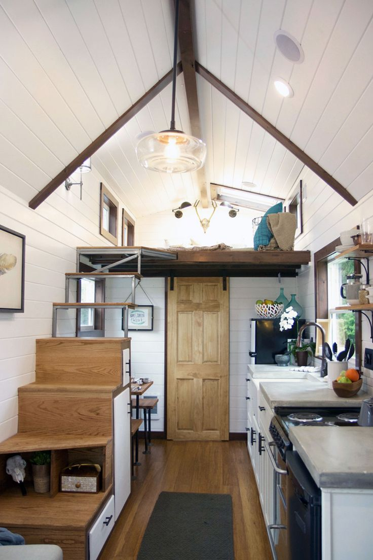 """This tiny house kitchen features a large farm sink, concrete countertops, an apartment size refrigerator, and a 24"""" four-burner electric range."""