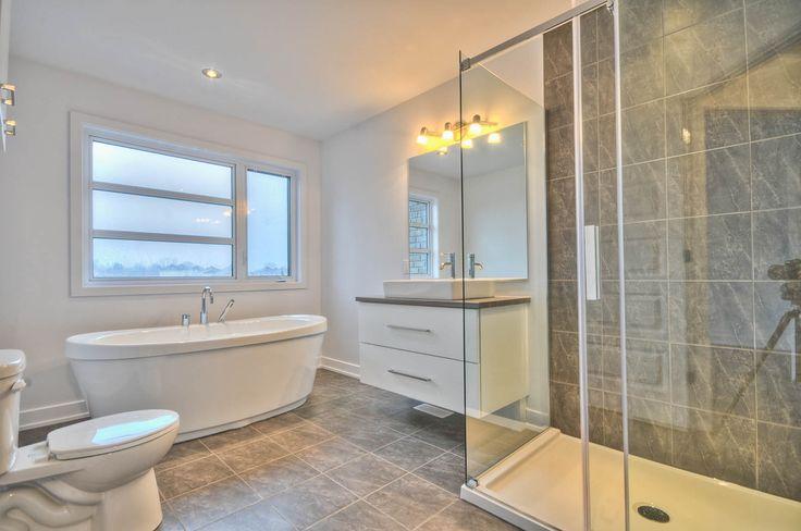 Salle de bain avec bain autoportant et douche en céramique.