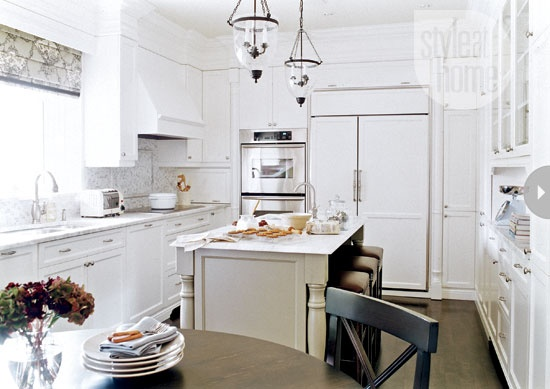 This family-friendly kitchen takes everyone into account – not just the grown-ups – with its easy-to-access cupboards and roomy island. The white-on-white scheme is bright and airy and still trendy today, as is the beige kitchen island with turned legs that looks like a standalone piece of furniture.